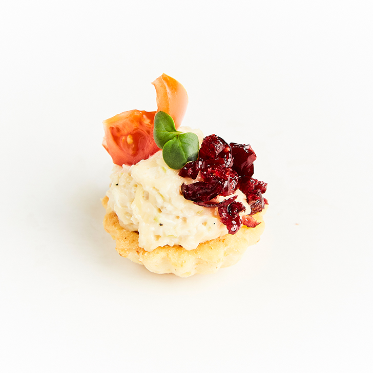 Small tart with cheese, pineapple, leek, smoked chicken salad and dried cranberry salsa