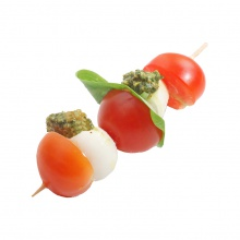 Mozzarella ball and cherry tomato skewers with basil pesto and herbs