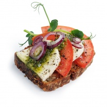 Whole grain bread slice with mocarella, tomatoes and basil pesto